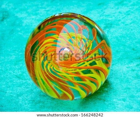 Glass marble ball with colorful swirl isolated on turquoise velvet background.