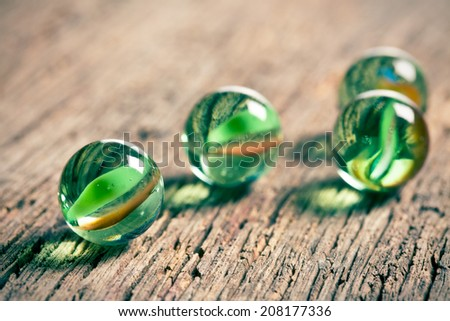 Glass marble balls on old wooden background - stock photo