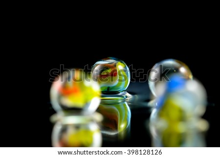 Glass marbles on water with black background - stock photo
