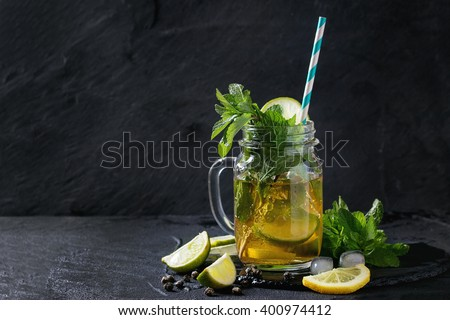 Glass mason jar of Ice green tea with lime, lemon, mint and ice cubes on black slate stone board over black textured background. With copy space