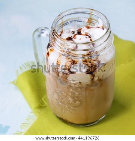 Glass mason jar with ice coffee with whipped cream, ice cream and chocolate sauce, served with coffee beans and ice cubes on green textile napkin over light blue textured background. Square image - stock photo