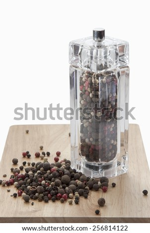 glass mill with with black, white and red peas pepper on a wooden board, isolated on white background.