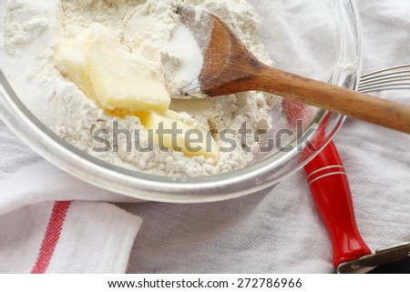 Glass mixing bowl with wooden spoon, butter and flour with pastry blender alongside on dish cloth - stock photo