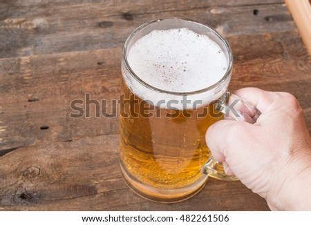 Glass mug of beer standing on an old wooden background, female hand holds