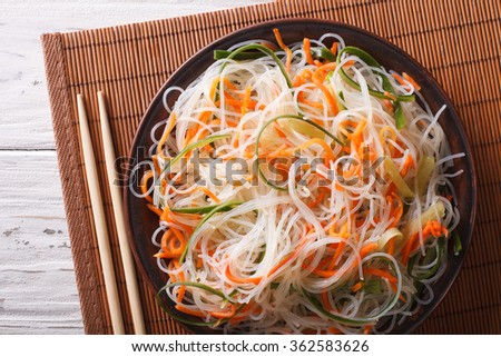 Glass noodle salad with cucumber and carrot on a plate close-up. horizontal top view - stock photo