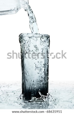 glass of a water with overflow isolated on white background - stock photo