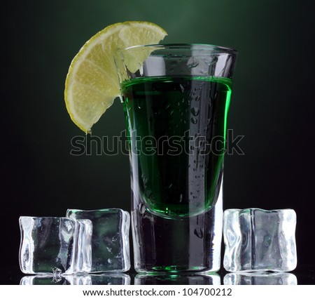 glass of absinthe, lime and ice on green background - stock photo