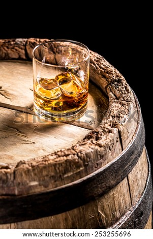 Glass of aged Scotch in the distillery basement - stock photo