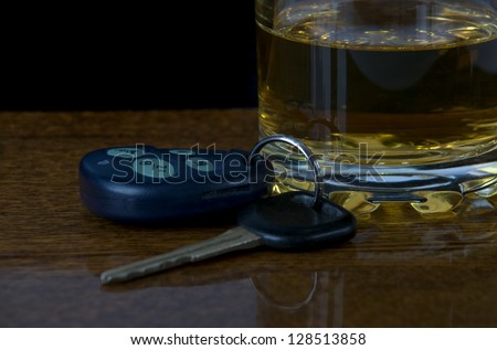 glass of alcohol and car keys on the bar