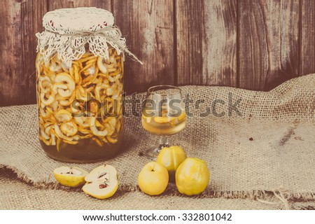 Glass of alcohol drink with quince fruits, vintage photo. - stock photo