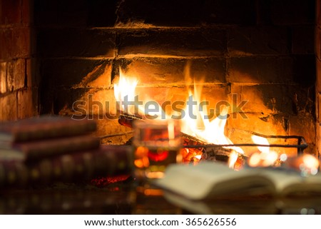 Glass of alcoholic drink wine and antique books in front of warm fireplace. Magical relaxed cozy atmosphere near  fire. Blurred focus