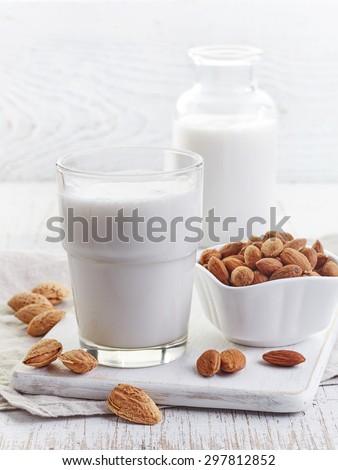 Glass of almond milk  on white wooden background - stock photo