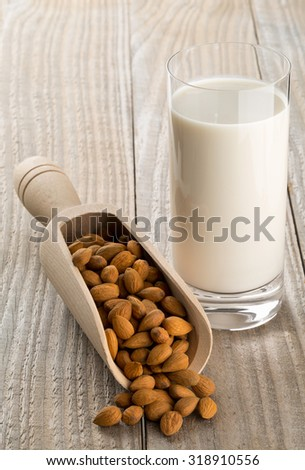 Glass of almond milk with shelled almond kernels on wooden table - stock photo
