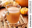 glass of apple cider with fall themed background. - stock photo