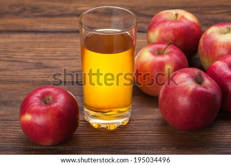 Glass of apple juice and red apples on wooden background - stock photo