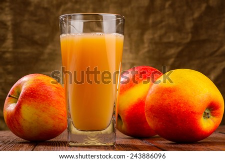 Glass of apple juice with apples on fabric background