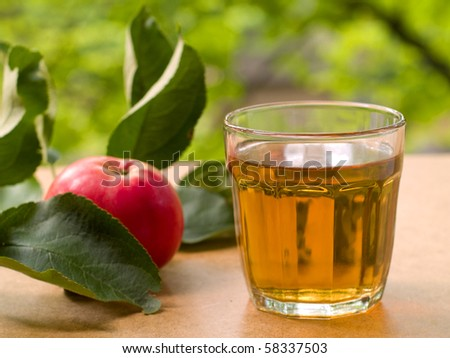 Glass of apple juice with apples on the background. - stock photo