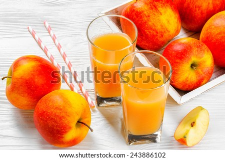 Glass of apple juice with apples on white wood background - stock photo