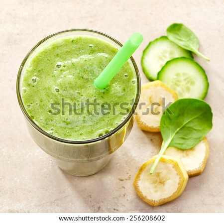 glass of banana, spinach and cucumber smoothie with a straw for healthy breakfast