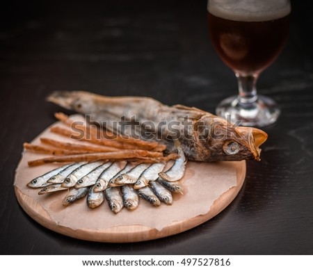 Glass of beer and assorted dried fish on a cooking sheet, traditional beer snack. Black wooden background.