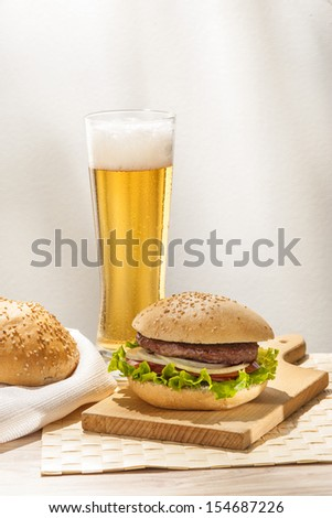 Glass of beer and cheeseburger  - stock photo