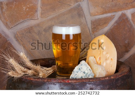 Glass of beer, cheese and ears on old barrel with iron rings - stock photo