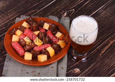 Glass of beer, cheese and smoked sausages plate - stock photo