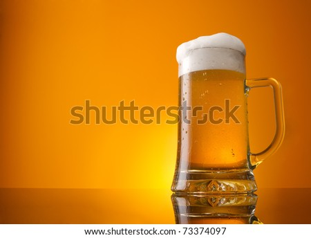 Glass of beer close-up with froth over orange background - stock photo