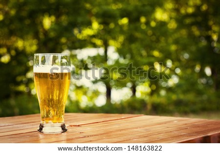 Glass of beer in nature - stock photo