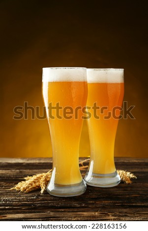 Glass of beer on a brown wooden background