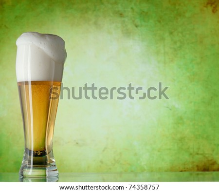 Glass of beer on a green background - stock photo