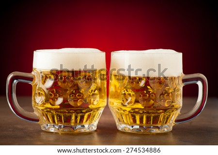 glass of beer on a stone table over a red background