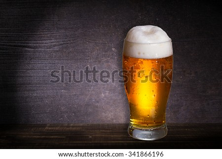 Glass of beer on dark wooden background