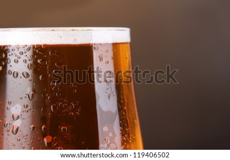 Glass of beer on grey background close-up - stock photo