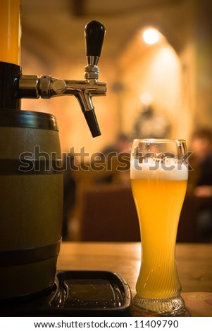Glass of beer on pub yellow background - stock photo