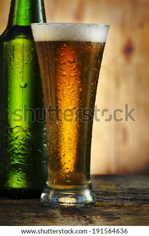 Glass of beer on rustic wooden table - stock photo