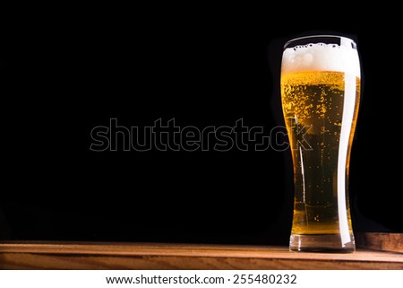 Glass of beer on wood table - stock photo
