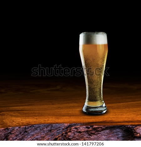 Glass of beer on wood table on black background