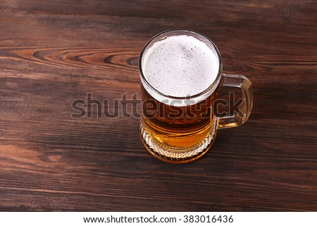 Glass of beer on wooden background - stock photo