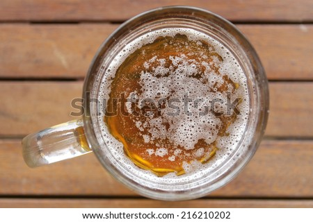 glass of beer on wooden desk top view - stock photo
