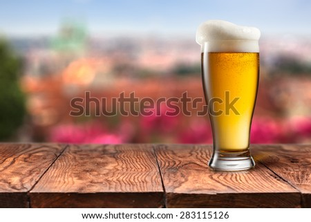 Glass of beer on wooden table with summer in Prague on background. Natural bokeh - stock photo