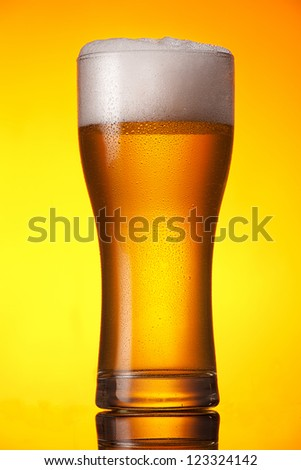 glass of beer over orange background - stock photo