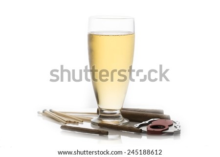 Glass of beer surrounded by cuban cigars, matches and cigar cutter - stock photo