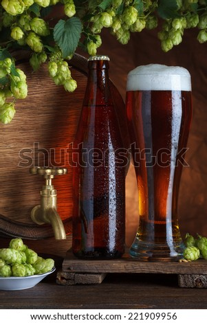 Glass of beer with barrel, bottle and fresh hops still-life
