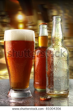 Glass of beer with bottles on counter - stock photo