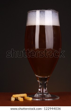 Glass of beer with crackers on brown background