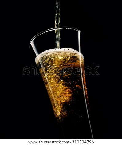 glass of beer with foam on a black background - stock photo
