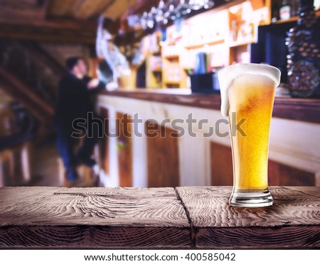 Glass of beer with foam on wooden table in bar background - stock photo