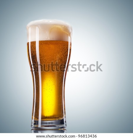 Glass of beer with froth close up on white background - stock photo