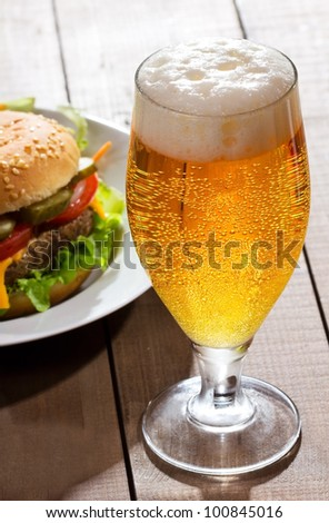 glass of beer with hamburger - stock photo